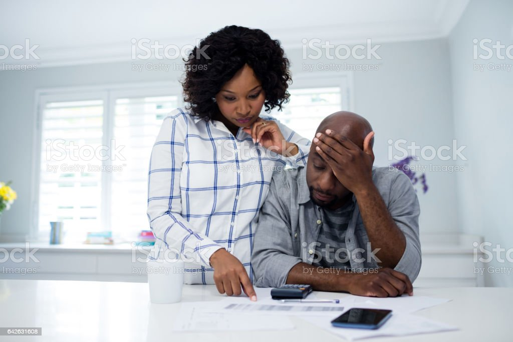 Worried couple interacting while checking the bills stock photo