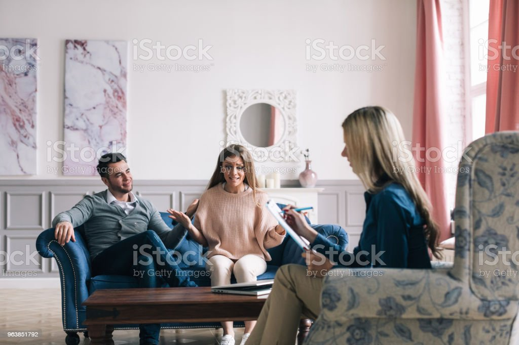 Worried couple listening to psychologist during a therapy sitting on a sofa at home. - Royalty-free Adult Stock Photo