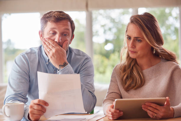 Worried Couple With Bills And Digital Tablet Sitting At Table At Home Reviewing Domestic Finances stock photo