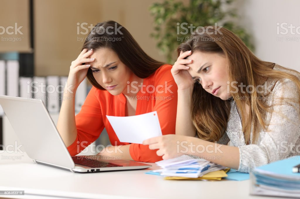 Worried coworkers reading a letter stock photo