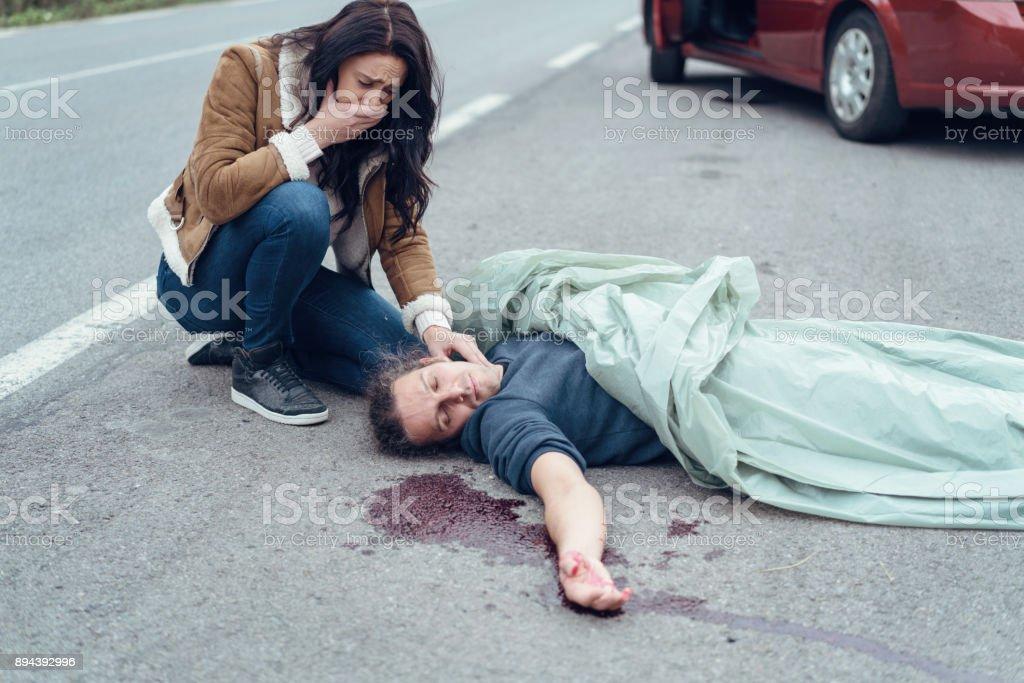 Mujer llora preocupada comprobando el pulso del herido - foto de stock