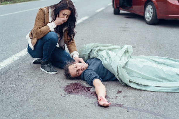 Worried crying woman checking the pulse of injured man stock photo