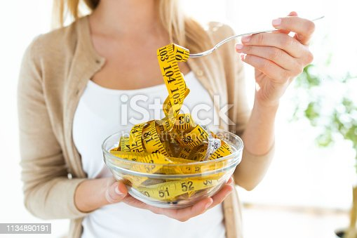 Worried cute woman holding bowl with measuring tapes at home.