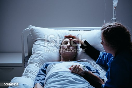 928968772 istock photo Worried daughter taking care of weak elderly mother with cancer 1006968932