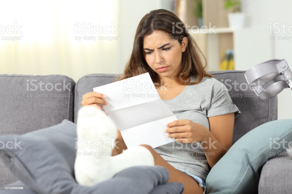 Worried disabled woman reading a letter stock photo