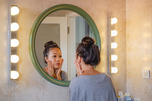 Rear view shot of a worried East Asian woman putting her hands on her cheek, checking her face skin from aging sign. She's standing in front a mirror with lights on both side.