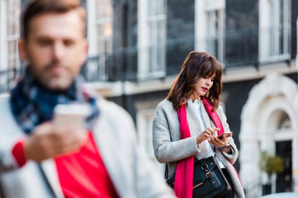 besorgt elegante frau mit smartphones im freien in der stadt - liebeskummer englisch stock-fotos und bilder