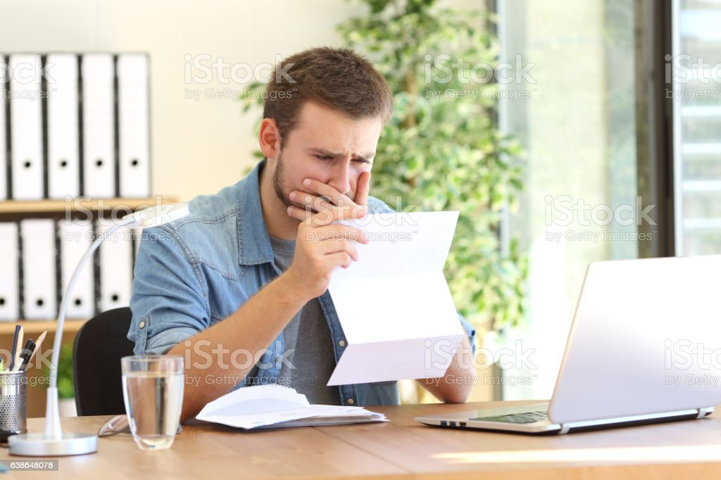 Worried entrepreneur reading a letter stock photo