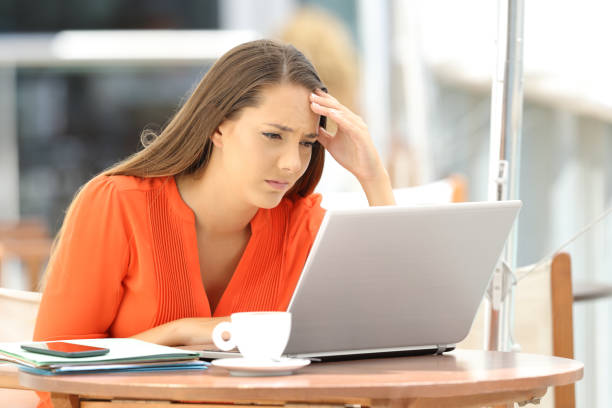 Worried entrepreneur reading bad news on line Worried entrepreneur reading bad news on line in a laptop sitting in a bar terrace low self esteem stock pictures, royalty-free photos & images