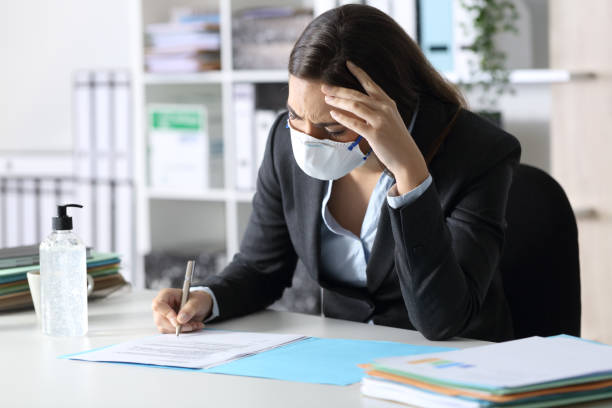 Worried executive wearing mask signing contract at office stock photo