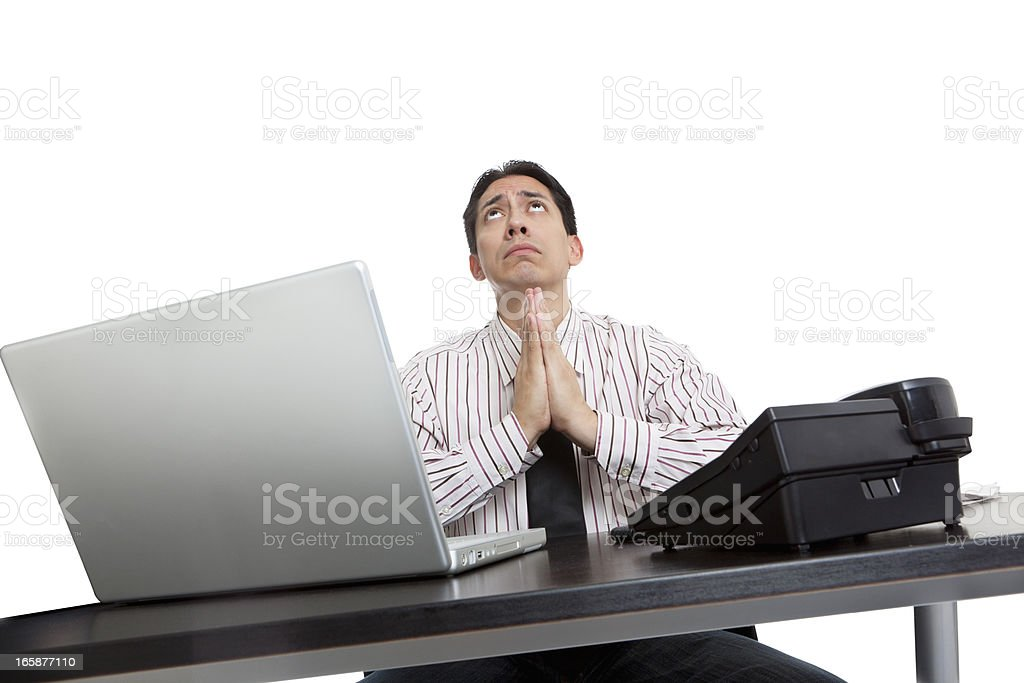 Worried executive with laptop and telephone praying royalty-free stock photo