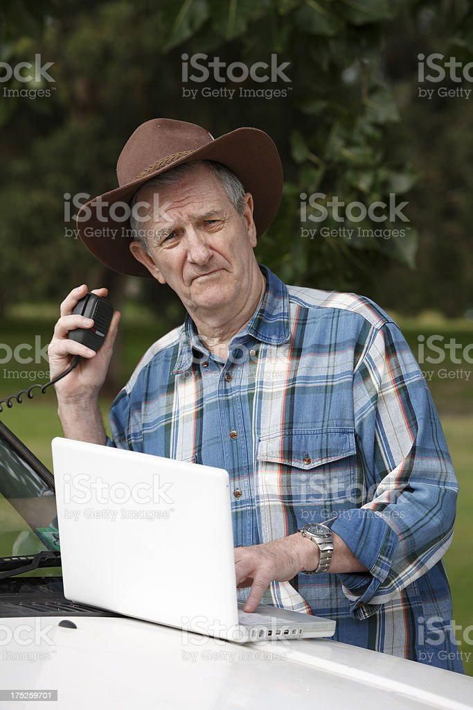 Worried farmer with computer on vehicle and radio stock photo