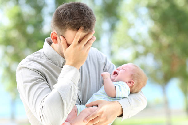 Worried father and baby crying stock photo