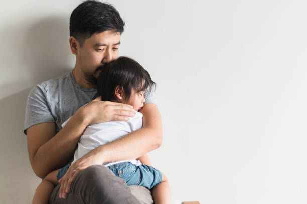 Worried father comforts ill son stock photo