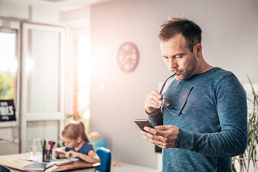 Worried Father Looking At Smart Phone Foto de stock y más banco de imágenes de Adolescente