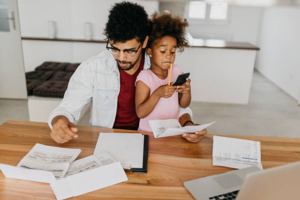 Worried father looking bills while child is sitting in his lap and she is using calculator stock photo
