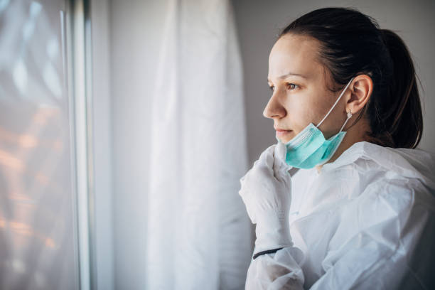 worried female doctor looking through the hospital window - personale sanitario foto e immagini stock
