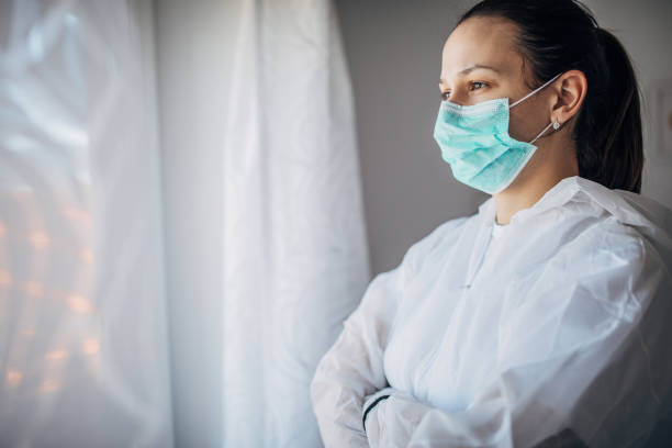 Worried female doctor looking through the hospital window stock photo