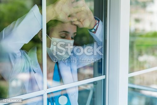 Worried female doctor looking through the hospital window