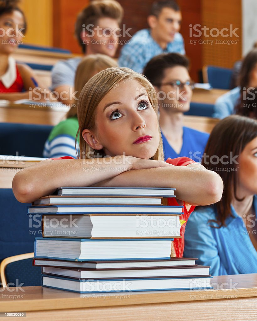 Worried female student Large group of high school students sitting in the lecture hall. Focus on the pensive young woman with piled up books, looking up. 20-24 Years Stock Photo