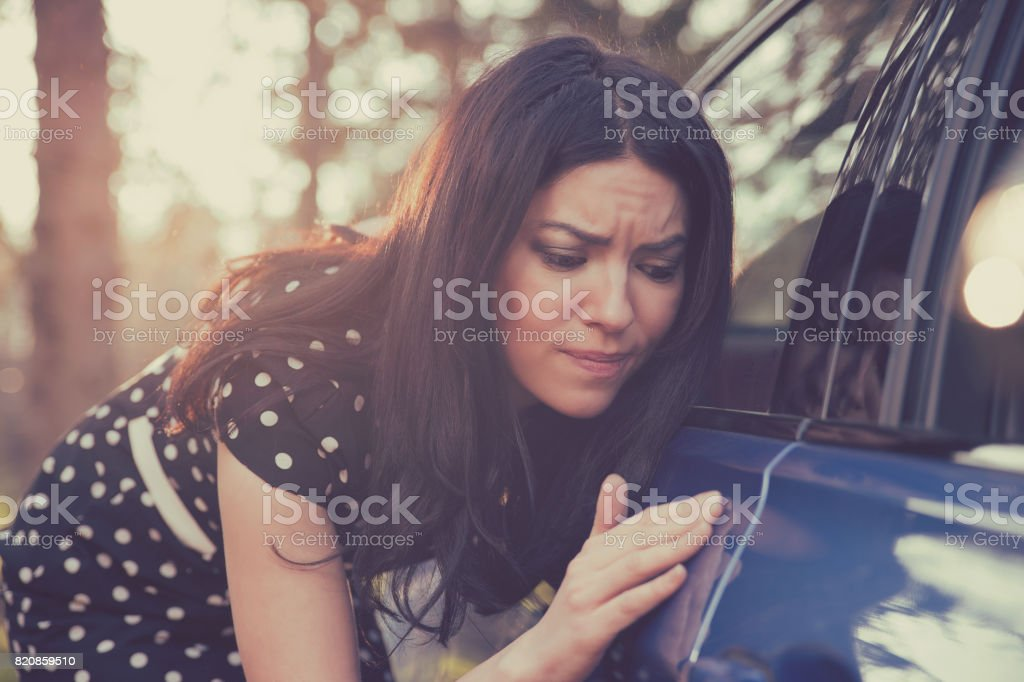 Worried funny looking woman obsessing about cleanliness of her car stock photo