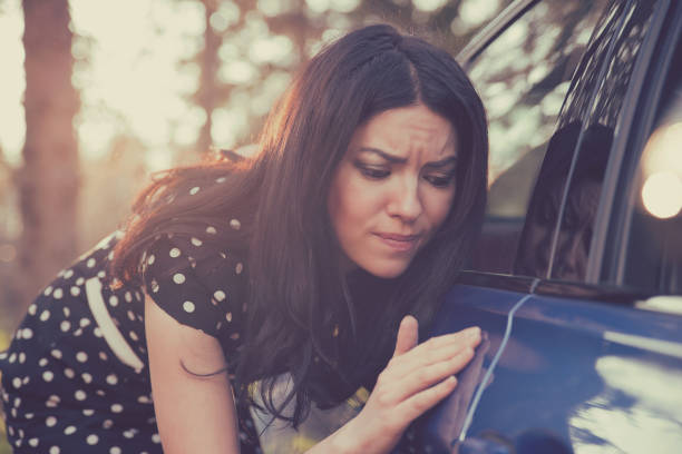 worried funny looking woman obsessing about cleanliness of her car - dent stock pictures, royalty-free photos & images