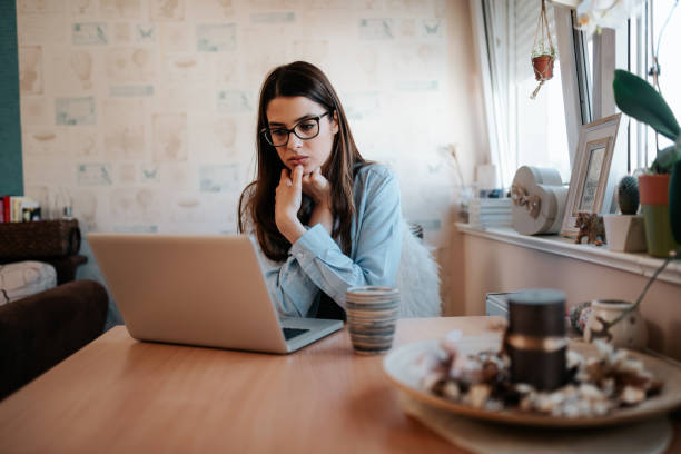Worried girl looking at laptop screen at home. Worried girl looking at laptop screen at home. worried stock pictures, royalty-free photos & images