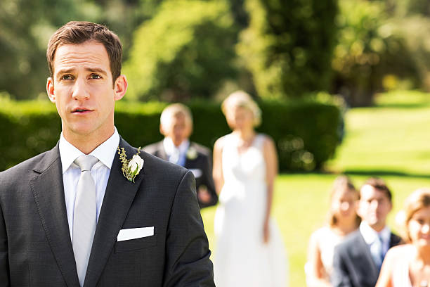 besorgt bräutigam wegsehen während der hochzeitsfeier - angst vor der geburt stock-fotos und bilder