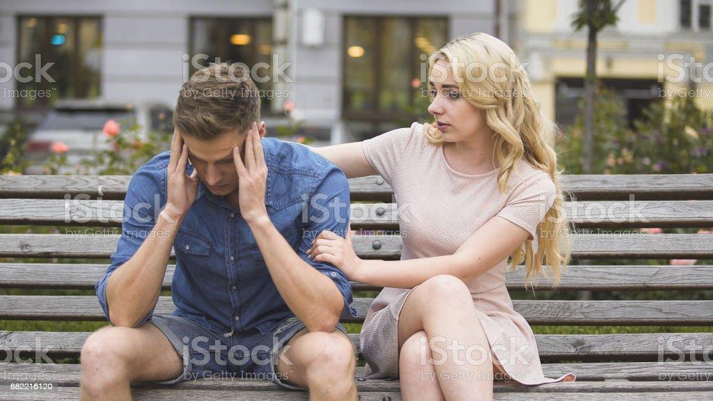 Cara de preocupado sentado na bancada, namorada ele acalmar, problemas e suporte - foto de acervo