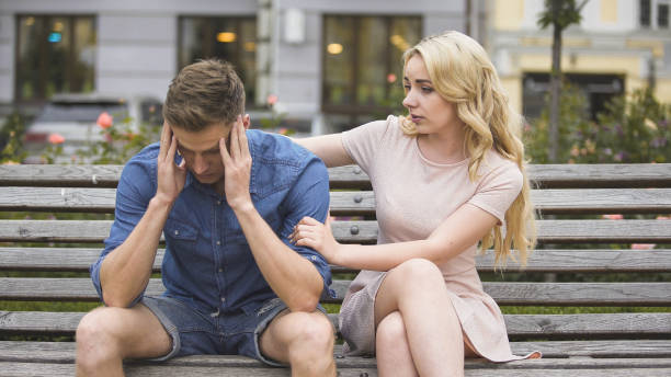 Worried guy sitting on bench, girlfriend calming him down, problems and support stock photo