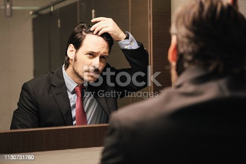 1130731761istockphoto Worried Hispanic Business Man Looking At Hairline In Office Restrooms 1130731760