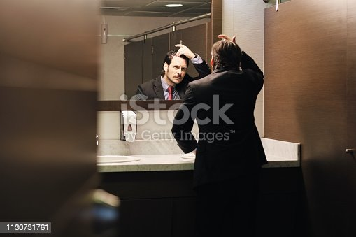 1130731761istockphoto Worried Hispanic Business Man Looking At Hairline In Office Restrooms 1130731761
