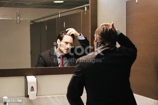 1130731761istockphoto Worried Hispanic Business Man Looking At Hairline In Office Restrooms 1130731766