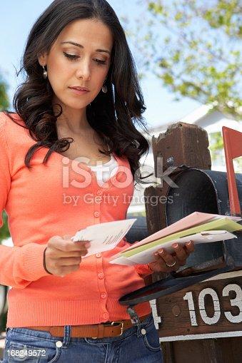 istock Worried Hispanic Woman Checking Mailbox 168249572