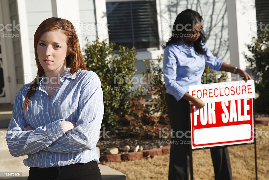 Worried Home Owner Outside Foreclosed House.See more of this series: