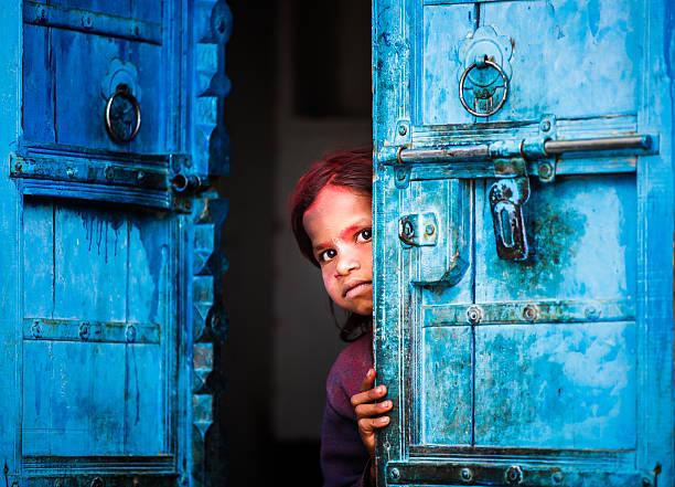 Worried indian girl behind a door stock photo