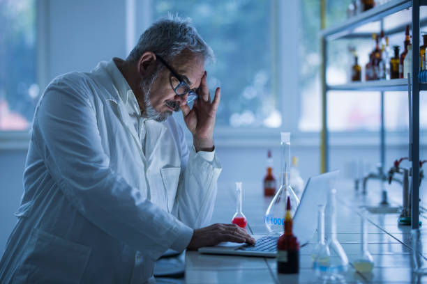 Worried lab worker working on laptop in laboratory. stock photo