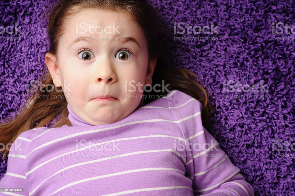 Worried Little Girl Lying on Purple Carpet Worried four-year-old girl lying on purple carpet.  What's in YOUR carpet? 4-5 Years Stock Photo