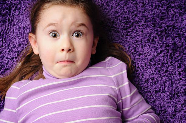 Worried Little Girl Lying on Purple Carpet stock photo