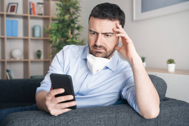 Worried man at home reading bad news about coronavirus contagion stock photo
