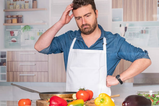 worried man before cooking at home for dinner - fail cooking imagens e fotografias de stock