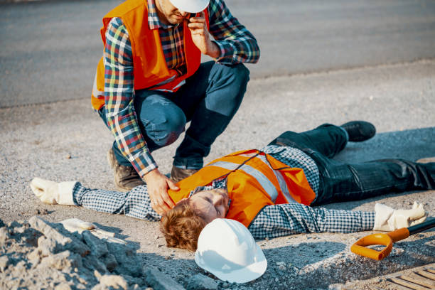 Worried man calling ambulance for his unconscious coworker stock photo