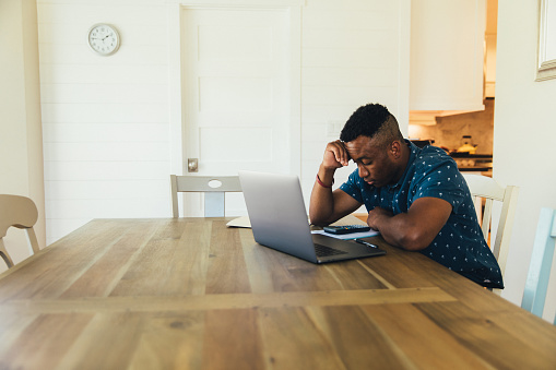A 30 year old man works on his finances at his kitchen table. He is working on his bank account numbers and preparing to pay his taxes. Times are tough and making ends meet is difficult.