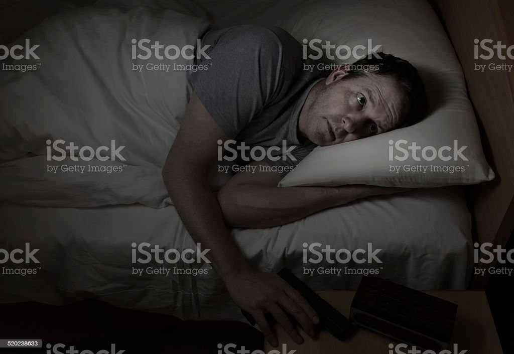 Worried man grabs gun from night stand while in bed stock photo