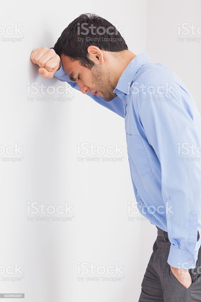 Worried man leaning his head against a wall stock photo
