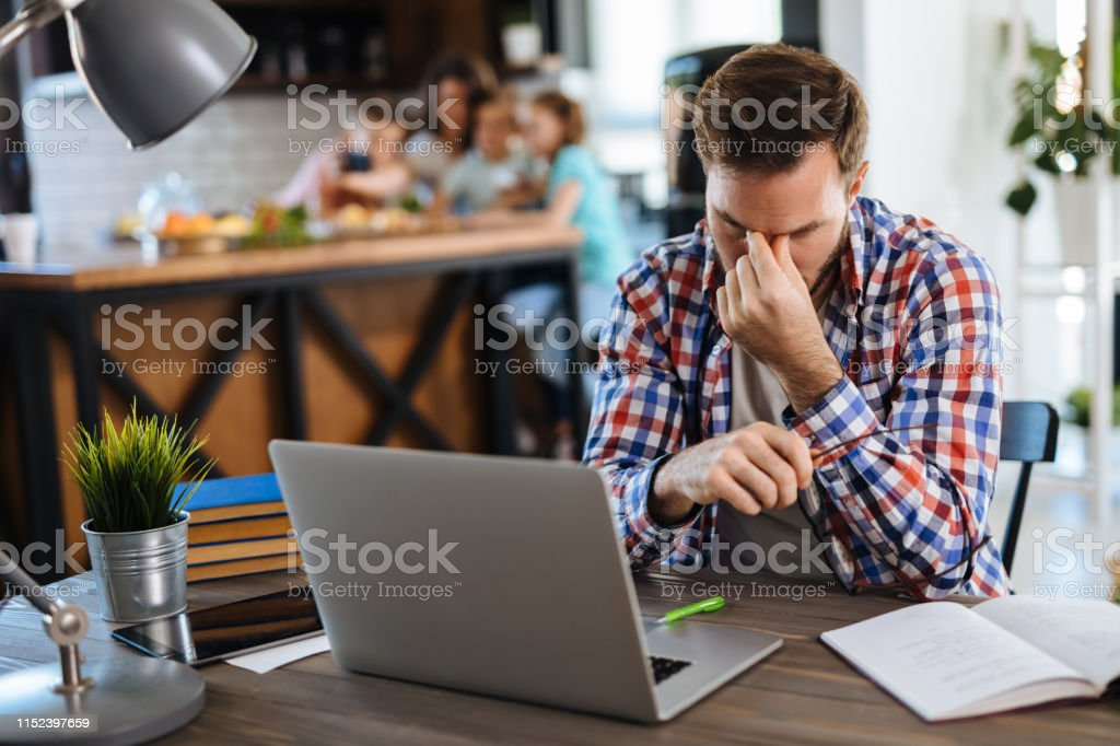 Worried man looking at his monthly bills at home