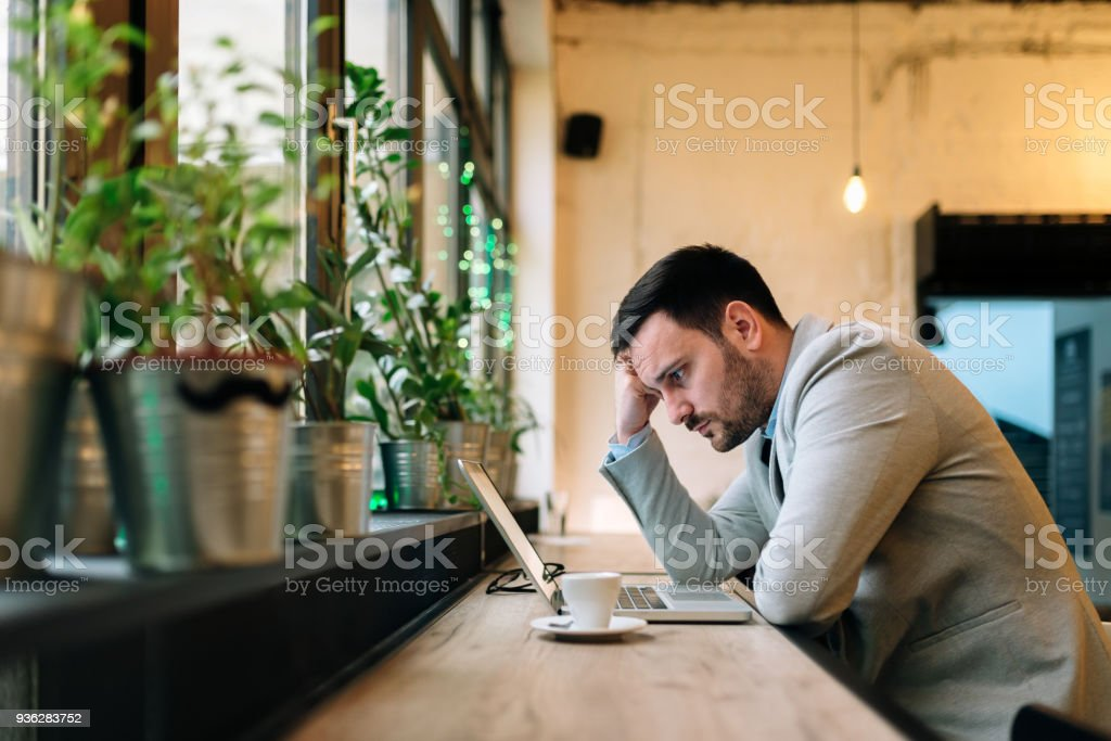Worried man looking at laptop screen while sitting at modern cafe. stock photo