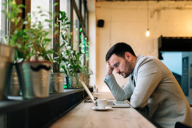 worried man looking at laptop screen while sitting at modern cafe. - worried stock pictures, royalty-free photos & images