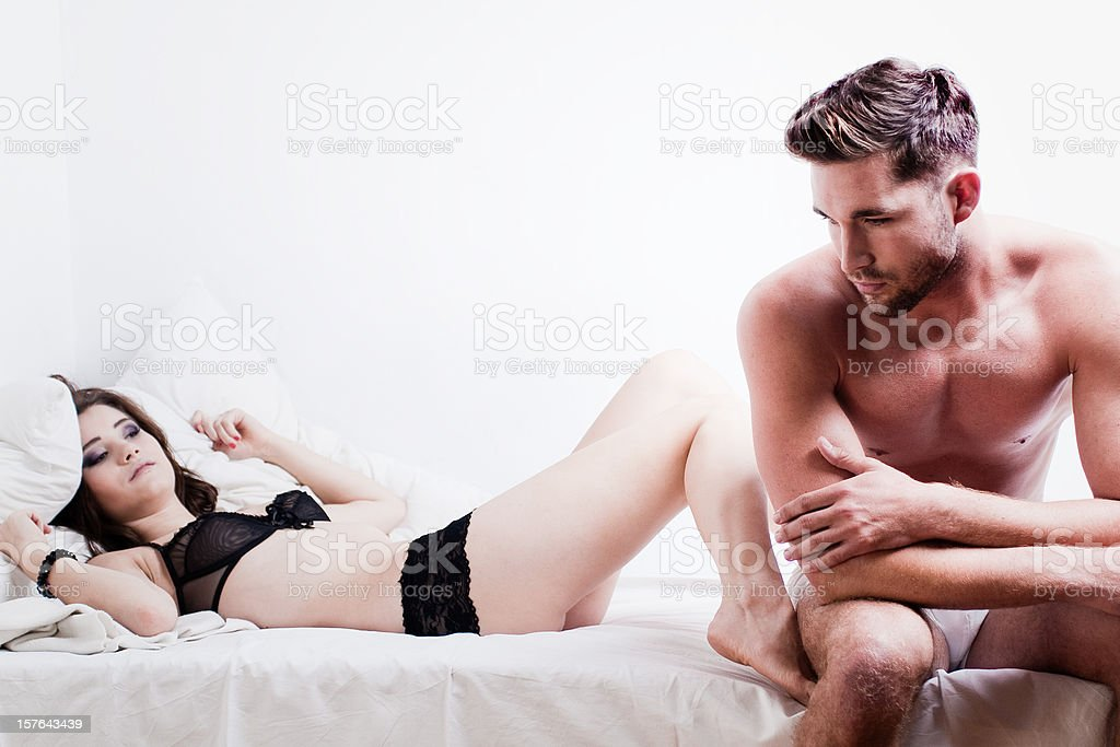 Worried man on edge of bed with impatient female partner stock photo