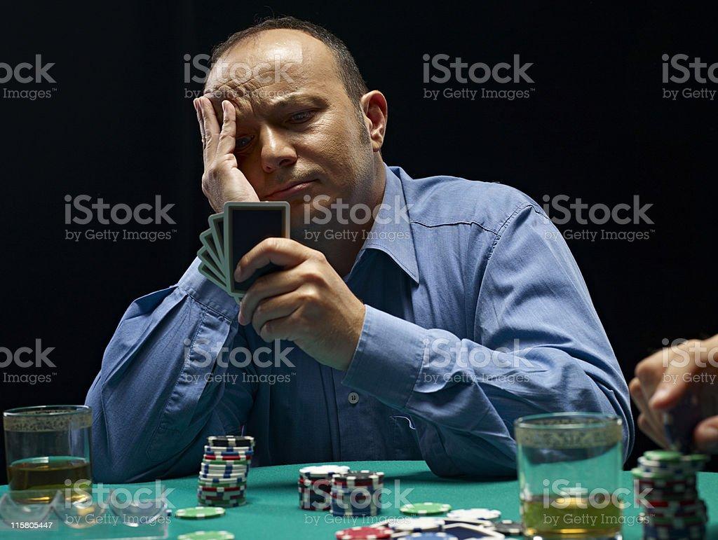 Worried man playing poker royalty-free stock photo